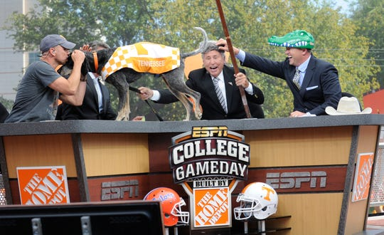 """Left to right, country music singer Kenny Chesney kisses UT football mascot """"Smokey"""" with analysts Lee Corso and Kirk Herbstreit as they pick who they think will be the game winner as ESPN College GameDay tapes their show from Circle Park on the University of Tennessee campus on Saturday, Sept. 15, 2012. Chesney appeared on the show as the guest game picker of the week."""
