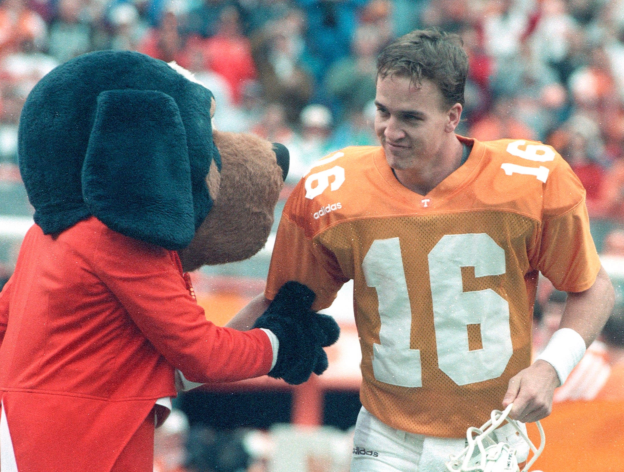 In a Nov. 29, 1997, photograph, Tennessee quarterback Peyton Manning greets Smokey before his final game at Neyland Stadium.