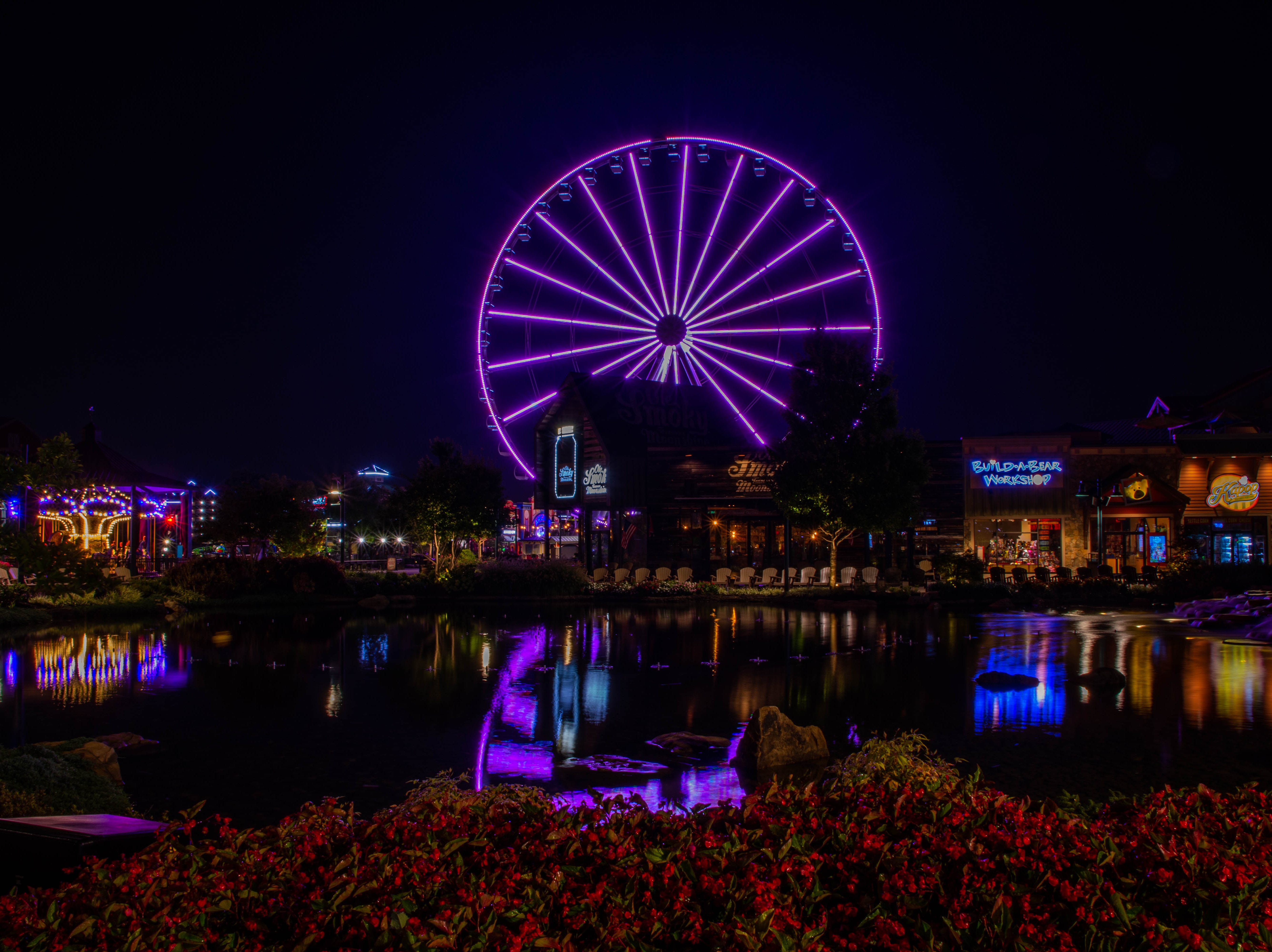 Lights reflect off the water at The Island in Pigeon Forge in Sevier County before sunrise on Monday, Aug. 27, 2018.