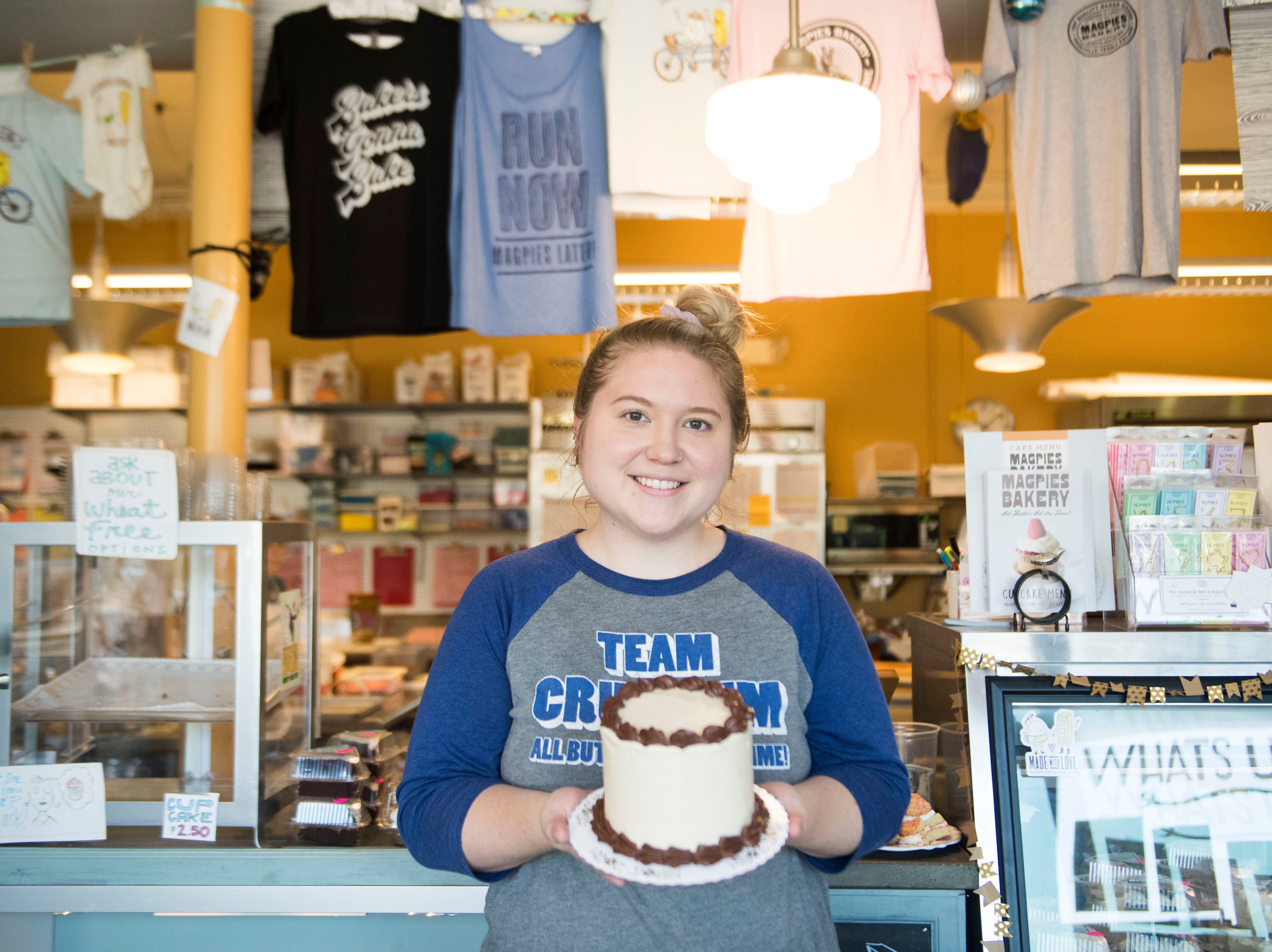 Elizabeth Smith, new owner of Magpies Bakery, located on North Central Street, stands with a cake in the shop's lobby Tuesday, Aug. 28, 2018. Smith bought the bakery from her aunt, Peg Hambright, in January.