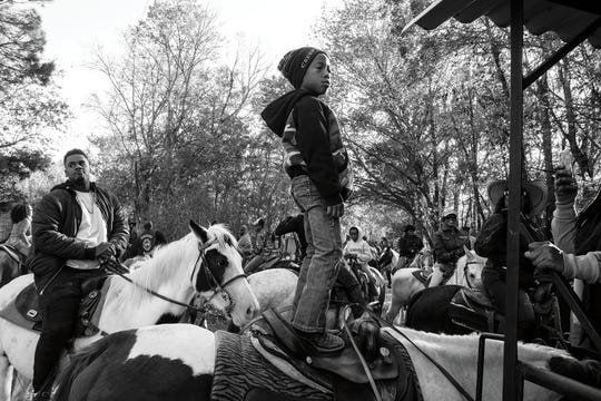"In this photo from the ""Louisiana Trail Riders"" book, a young rider stands on his horse during the 2017 Blinged Out Riders trail ride in St. Landry Parish."
