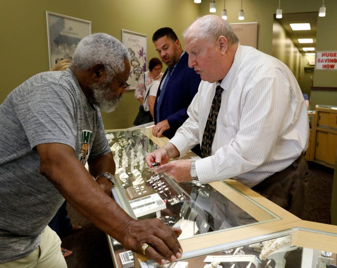 Stuart Palestrant shows a pair of earrings to Chuck Williams, from Reynoldsburg, Tuesday afternoon, Aug. 28, 2018, at Wendel's Diamond Jewelers in Lancaster. Palestrant is retiring after 40 years of working at the store and owning it for the last 30 years.