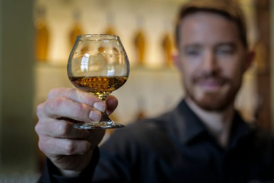 Mike Bohn, beverage manager, holds up a glass of bourbon, showing off the legs formed on the walls of the glass from swirling, inside Angel's Envy Distillery on Tuesday, August 28, 2018 in Louisville, Ky.