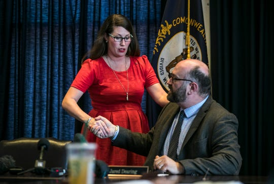 Alison Lundergan Grimes, Kentucky Secretary of State, shakes the hand of Jared Dearing, who wrote a nine-page report that accused her of abusing her office.  August 28, 2018