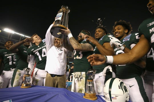 Head coach Mark Dantonio holds up the winning trophy along with players Chris Frey #23, Brian Lewerke #14, and Damion Terry #6 of the Michigan State Spartans after defeating the Washington State Cougars 42-17 in  the SDCCU Holiday Bowl at SDCCU Stadium on December 28, 2017 in San Diego, California.