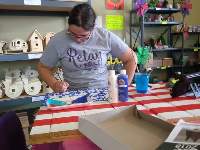 Manitowoc Glaze and Paint owner Katie Schamburek works on a piece for Relay for Life.