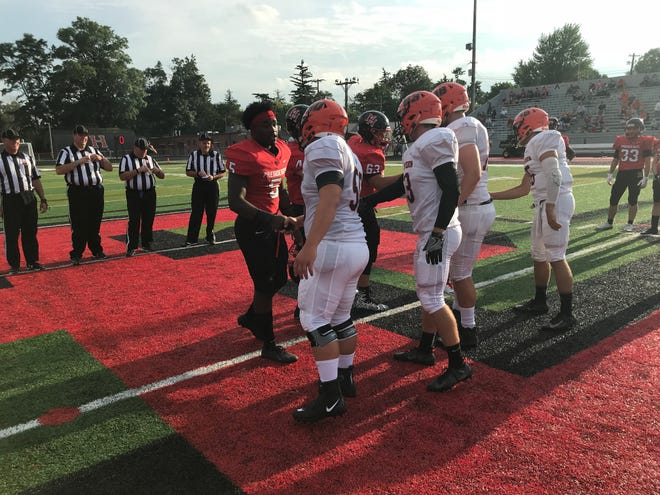 Marion Harding's captains shake hands with Mount Vernon after the coin toss Friday night in Harding Stadium. The Presidents won 21-12 and will host Jonathan Alder this Friday.