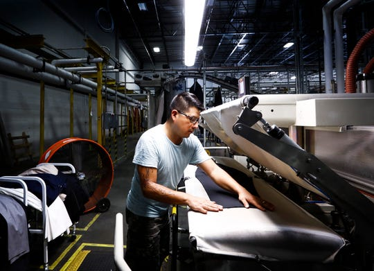 Suit-Up Inc. employee Ismael Garcia presses dress pants that will be packaged and shipped from their warehouse in South Memphis.