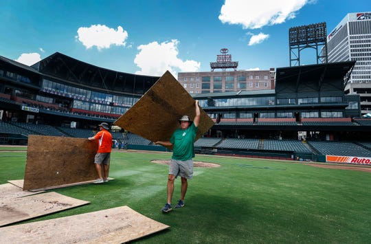 Diamond Design's Geoffrey King carries of plywood sheets during the early stages of transforming AutoZone Park baseball field into a soccer pitch for Saturday's ÒSoccer ShowdownÓ exhibition match.
