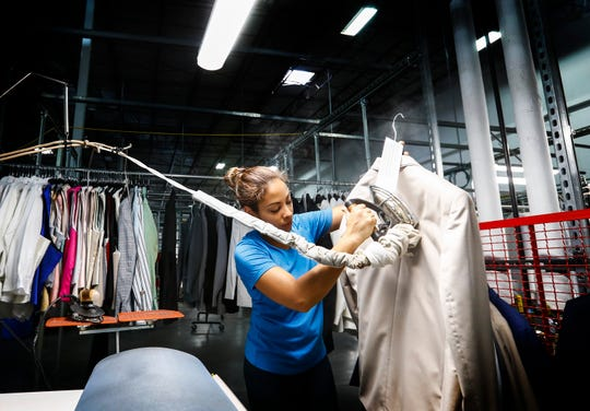 Suit-Up Inc. employee Ema Fernandez steams presses a suit that will be packaged and shipped from the warehouse in southeast Memphis.
