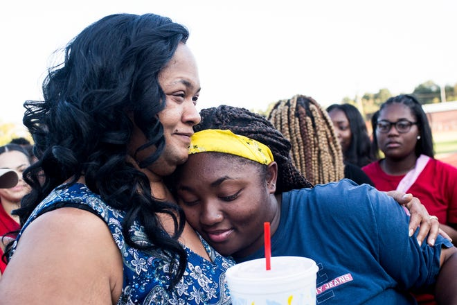 August 27 2018 - Tracy Mitchell and her daughter, Toni, hug after a balloon release in honor of Dennis Mitchell at Byhalia High School football field. Mitchell,Êa sophomore football player, collapsed on the field and died Friday night during a game.