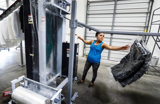 Suit-Up Inc. employee Maria de Jesus Vazquez Moreno packages dry-cleaned formal wear for shipment. Tip Top Tux of Sioux City, Iowa, recently bought the Memphis tuxedo warehouse Suit-Up Inc. and Xedo Inc. from ACS Clothing Group.