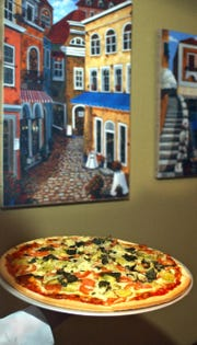 Trattoria di Carlo in Oak Creek features pizza with recipes going back decades. One of chef and owner Carlo Pedone's favorites is the Sicilian served with tomatoes, basil and artichokes.