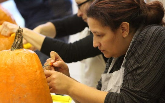 Carletta Copus of Milwaukee carves one of 370 pumpkins that volnteers cleaned and carved at the Wehr Nature Center for the family-friendly Halloween Haunts that sets out lit jack-o-lanterns on Wehr's nature trails.