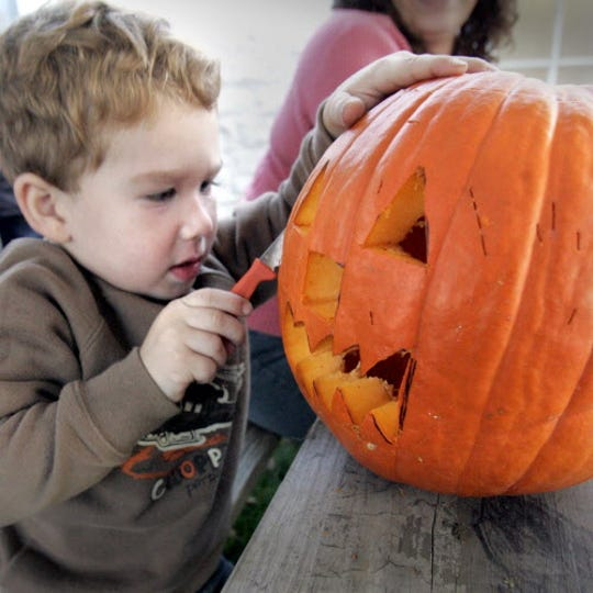Austin Hoffman, 3, digs into the pumpkin he helped create at the 3rd Pumpkin Pavilion at Humbolt Park hosted by the Bay View Neighborhood Association.