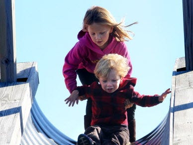Addy Probst helps her brother Grant onto a burlap mat for a trip down a giant slide on Sept. 30 at the Lindner Farm on National Avenue that offers a petting zoo, pumpkins and other seasonal activities
