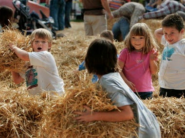 Children take time from stuffing straw into scarecrows they were building to engage in a straw fight as part of the annual Harvest Fair at State Park.