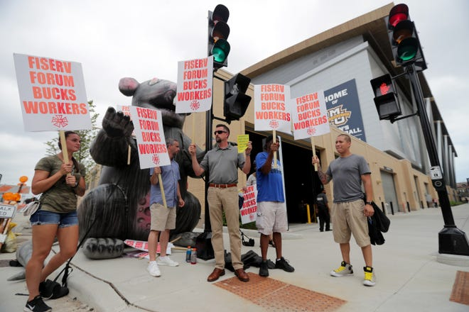 People representing IATSE Local 18 hold signs protesting wages for stagehands outside the Fiserv Forum on Tuesday, August 28, 2018.