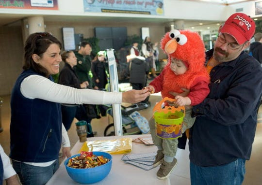 "Dressed as Elmo from ""Sesame Street,"" Henry Baisley, 2, of West Allis, is tickled to get candy at the Milwaukee County Zoo's Halloween Trick-or-Treat Spooktacular."