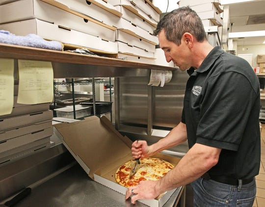 Ricardo's Pizza owner Rich Loch prepares a pizza at his Greendale restaurant.