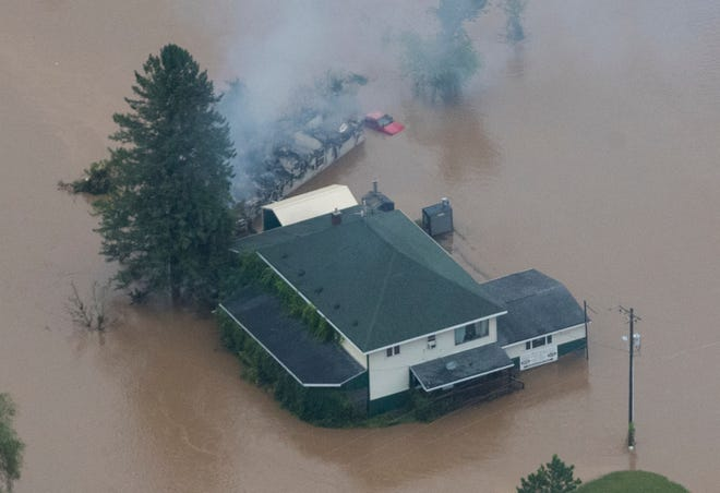 The remains of a trailer home smolder in the floodwaters.