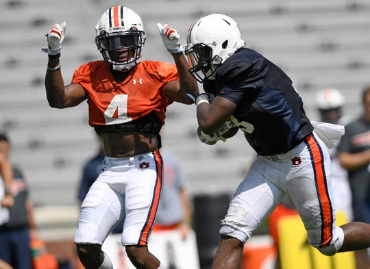 Auburn cornerback Noah Igbinoghene (4) attempts to tackle running back JaTarvious Whitlow during a scrimmage on Wednesday, Aug. 15, 2018 in Auburn, Ala.