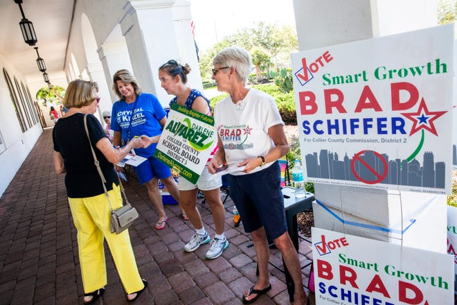 Robin Sheley, from second from left, Courtney Hemmer and  Donna Caron speak to an incoming voter in the solicitation zone to encourage them to cast their ballot for their respective candidates at the Collier County Public Library Headquarters in North Naples on Tuesday, Aug. 28, 2018.