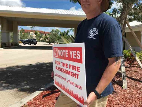 A campaigner at Naples Church of Christ holds a sign in favor of the North Collier fire fee.