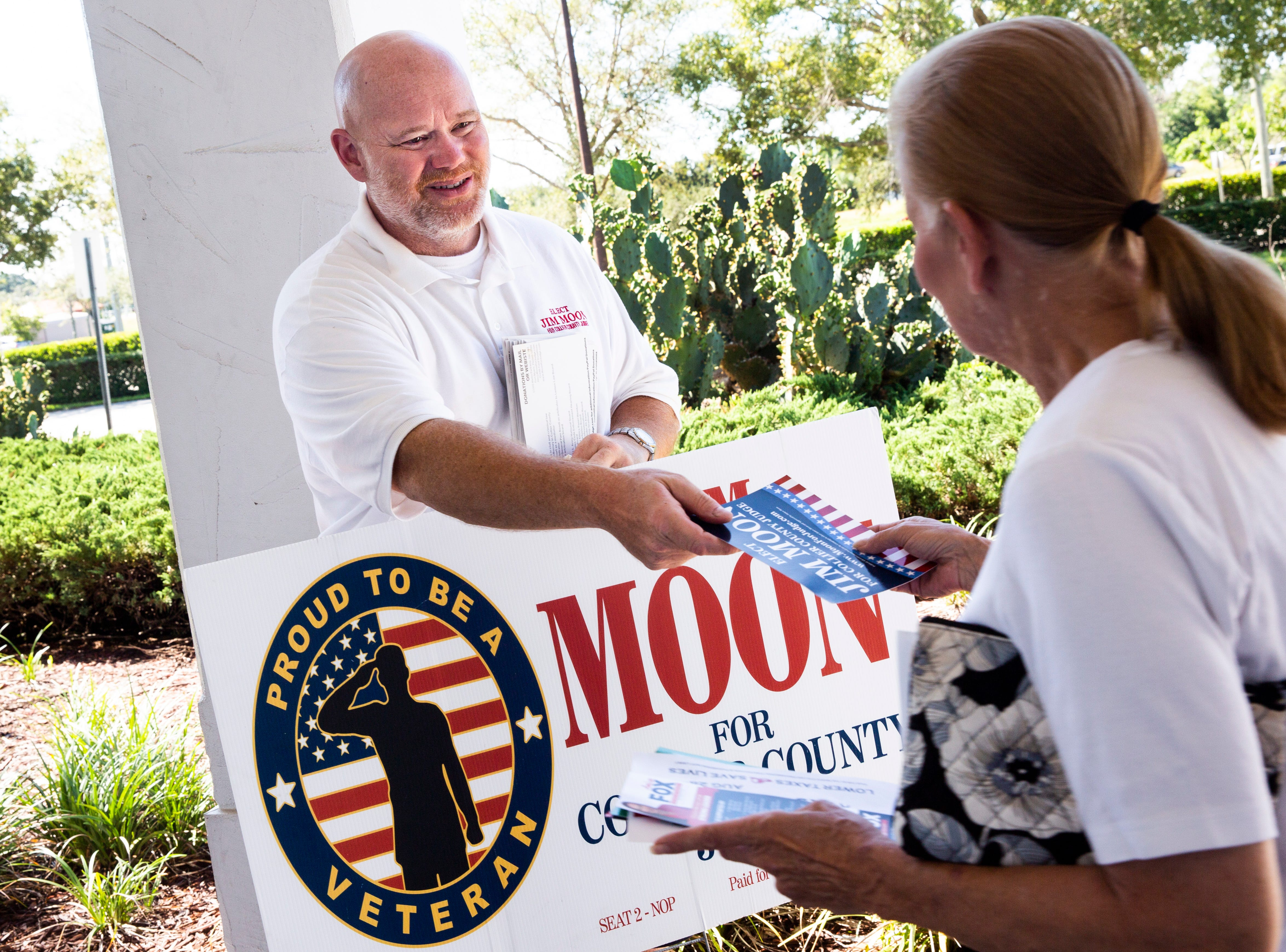 Jim Moon, who is running for Collier County Judge, hands out a leftlet to an incoming voter at the Collier County Public Library Headquarters in North Naples on Tuesday, August 28, 2018.