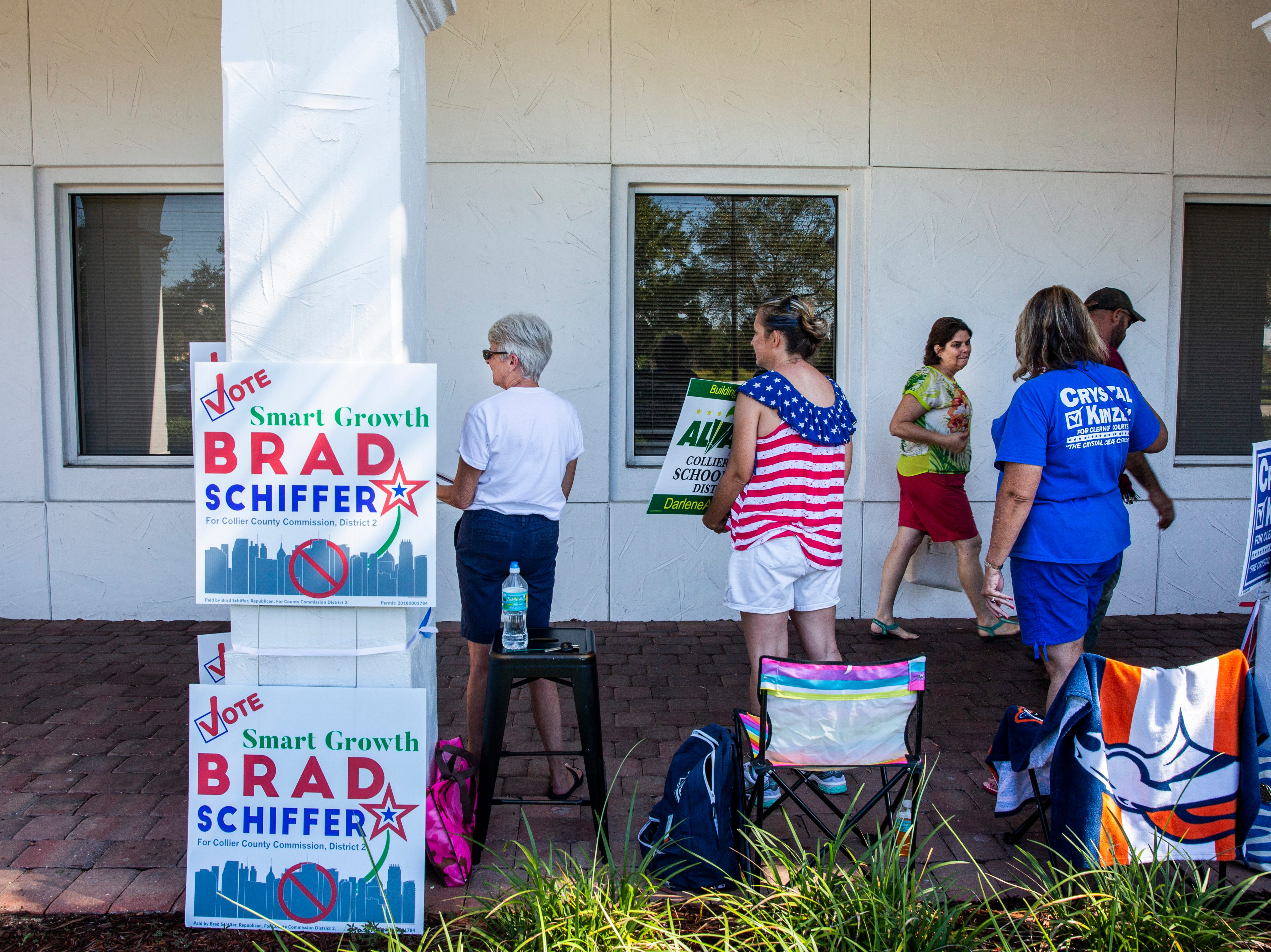 Incoming voters walk through the solicitation zone as Robin Sheley, from right, Courtney Hemmer and Donna Caron encourage them to cast their ballot for their respective candidates at the Collier County Public Library Headquarters in North Naples on Tuesday, August 28, 2018.