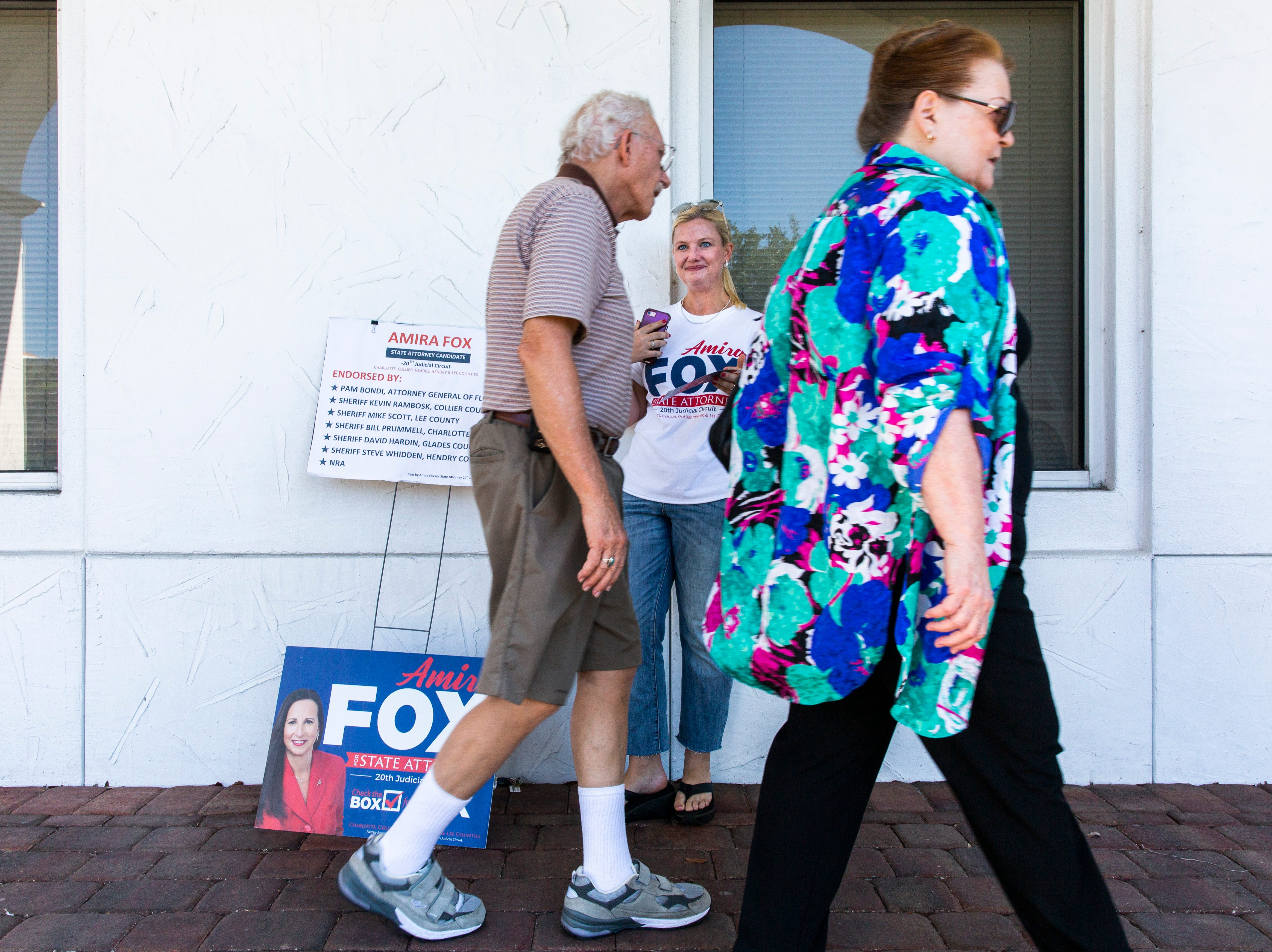 Kate Rumley encourages voters on their way in to cast their ballot for Amira Fox at the Collier County Public Library Headquarters in North Naples on Tuesday, August 28, 2018.