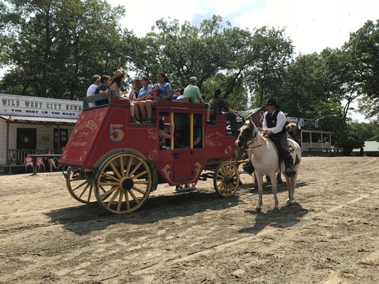 The marshal at Wild West City, a western-themed seasonal park in Byram, N.J., checks in on stagecoach passengers on Aug. 15, 2018.