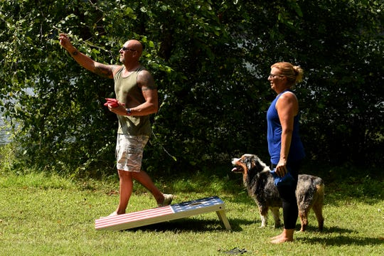 A hot summer day at Ramapo State Forest in Oakland on Tuesday August 28, 2018. Dan Porsch from Mahwah and Natalie Moretti from Hoboken, play cornhole as Montana(the dog) watches.
