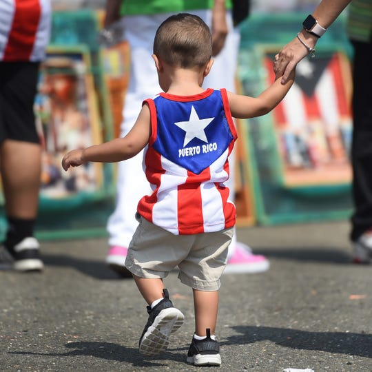 Sebastian Haper (age 1) of Paterson, holds the hand of his mother Keishla Santiago (R) during the Puerto Rican Festival in Paterson on 08/26/18. (Mitsu Yasukawa/@mitsuyasukawa)