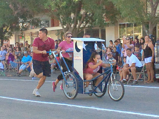 One-on-One Fitness raced to the finish line first in the coed division of Saturday's Busy Bee Septic Great American Outhouse Race on historic Silver Avenue. Pushing, from left, are Anthony Lopez, Crystal Peña and Jordan Ramirez. Steering the outhouse is Nadine Ramirez.