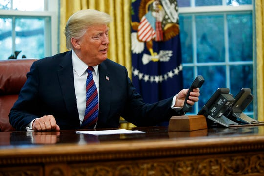 President Donald Trump hangs up after talking with Mexican President Enrique Pena Nieto on the phone in the Oval Office of the White House, Monday, Aug. 27, 2018, in Washington.