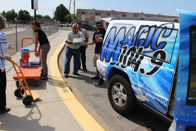 "Las Cruces Public Schools employees receive supplies from Ricky T and Patricia Valencia of Magic 104.9. The supplies were collected at the station's eighth annual ""Stuff the Bus"" campaign."
