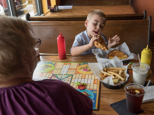 Linda Johnson and her 5-year-old grandson Drew Knysz celebrate his first day of kindergarten with lunch and a game of Parcheesi at the New Hudson Cafe.