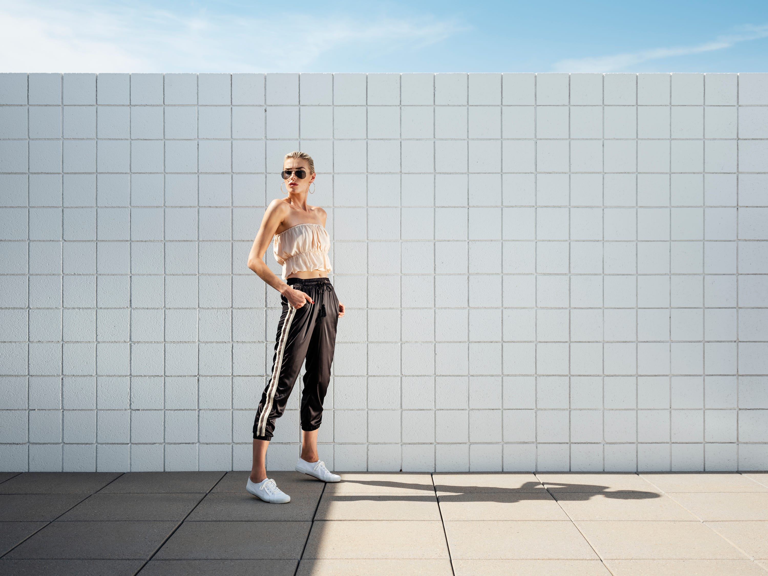 Loyd/Ford top and joggers, at loydford.com. Tennis shoes, sunglasses and earrings, stylist's own. (Styling by Neil Cohen; hair and makeup by Chelsea Dorris; model: Milena Ilina; creative direction: Kristin Scharkey; location: Desert One, Palm Springs)