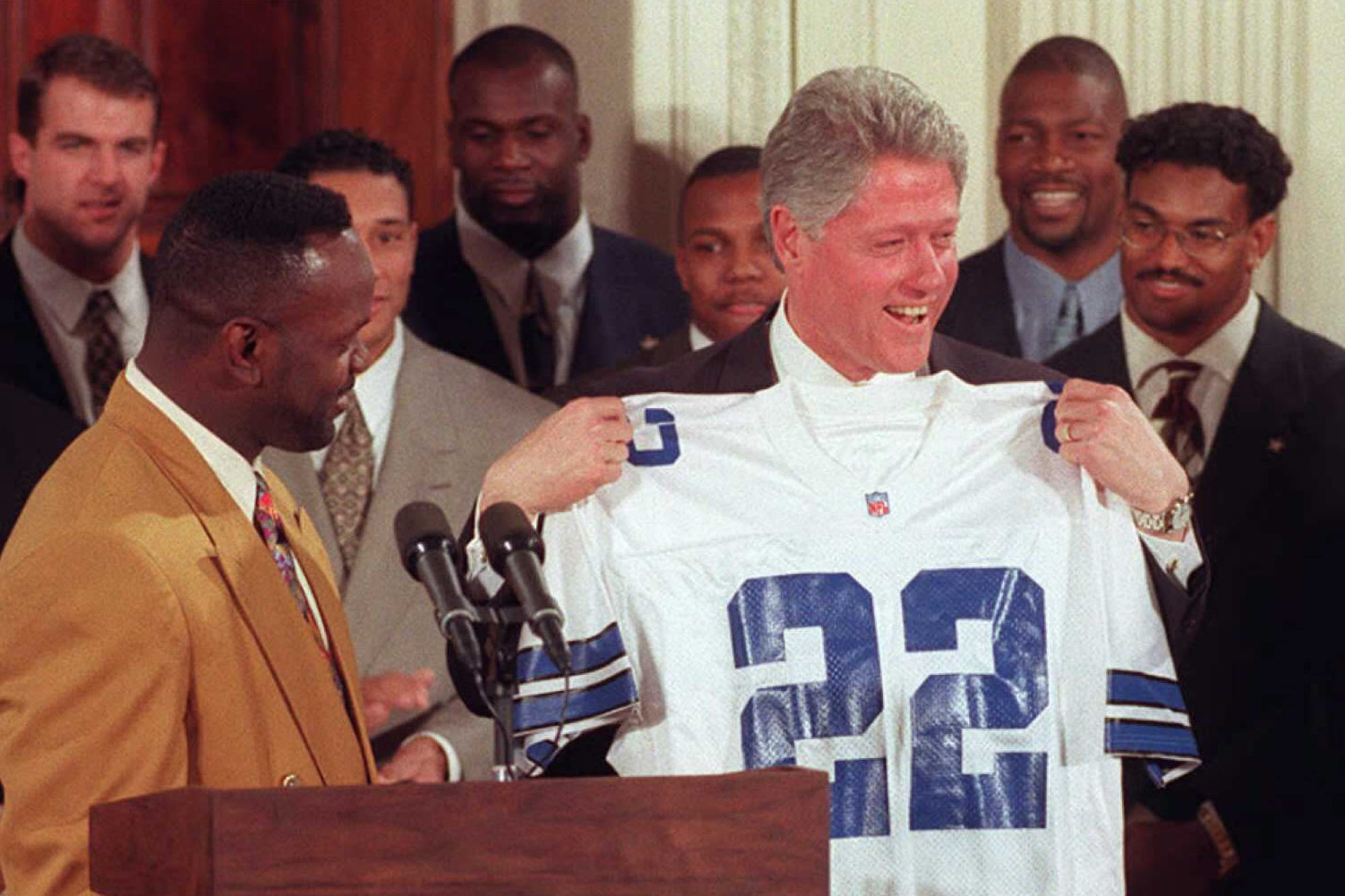 WASHINGTON, DC - FEBRUARY 13:  US President Bill Clinton (R) holds a Dallas Cowboys jersey presented to him by running back Emmitt Smith (L) bearing Smith's number during a ceremony 13 February at the White House to honor the Cowboys for their 28 January win in Super Bowl XXX. At rear are other members of the team.  (Photo credit should read JOYCE NALTCHAYAN/AFP/Getty Images)
