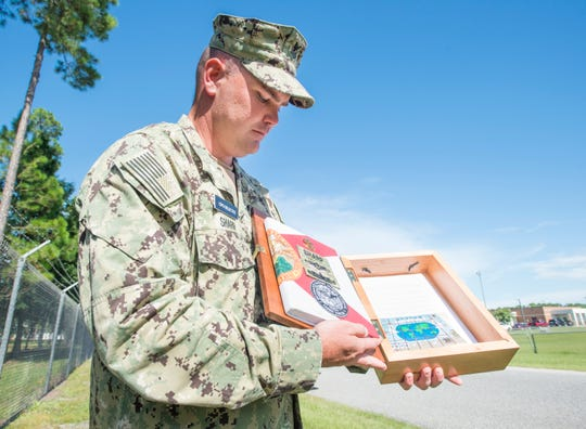 Kees Sharp, a chief petty officer selectee, shows off his Florida-themed charge book Aug. 27 outside Corry Station.