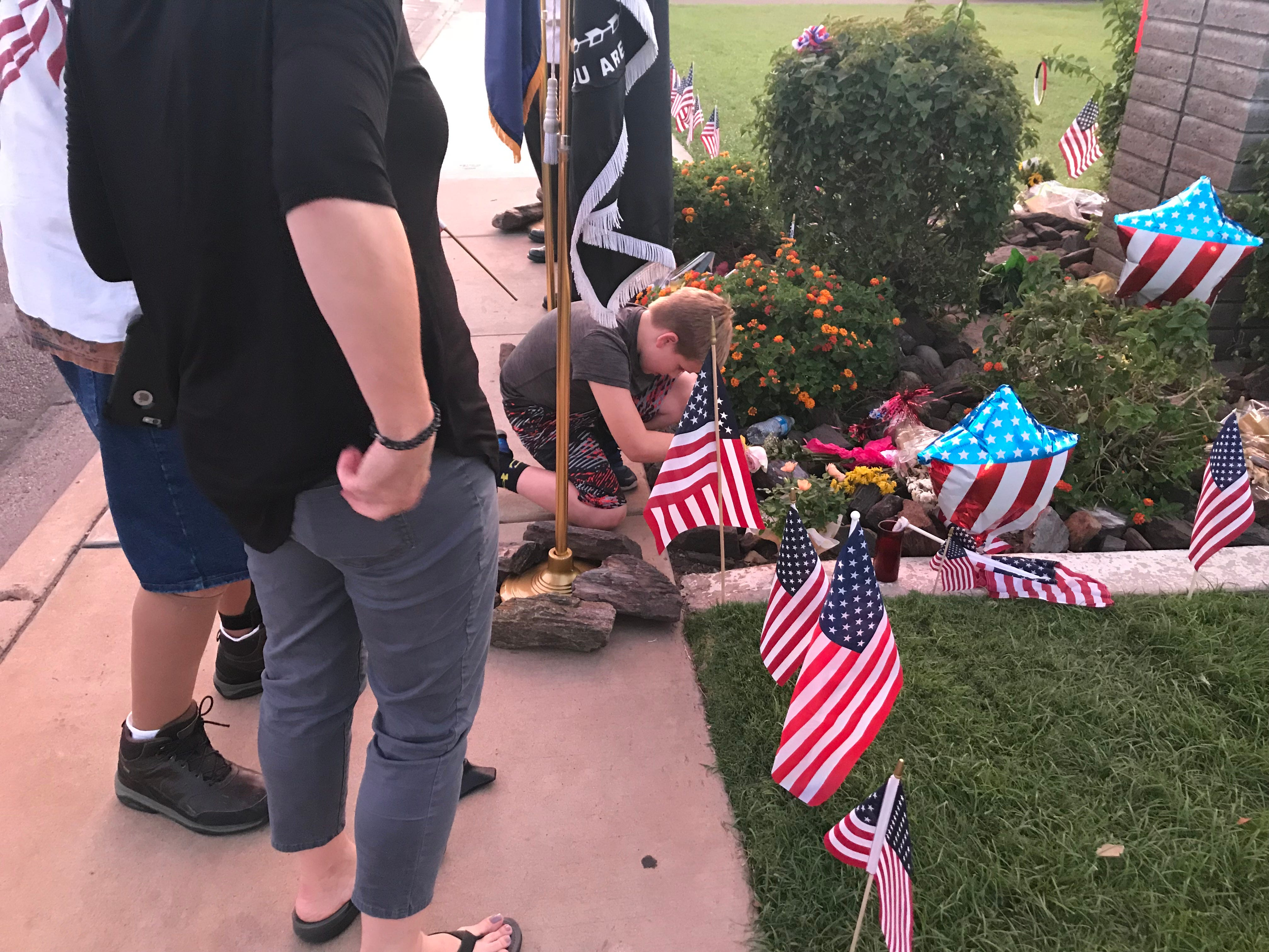 Boy pays respects to McCain by setting flag down at Phoenix Mortuary.