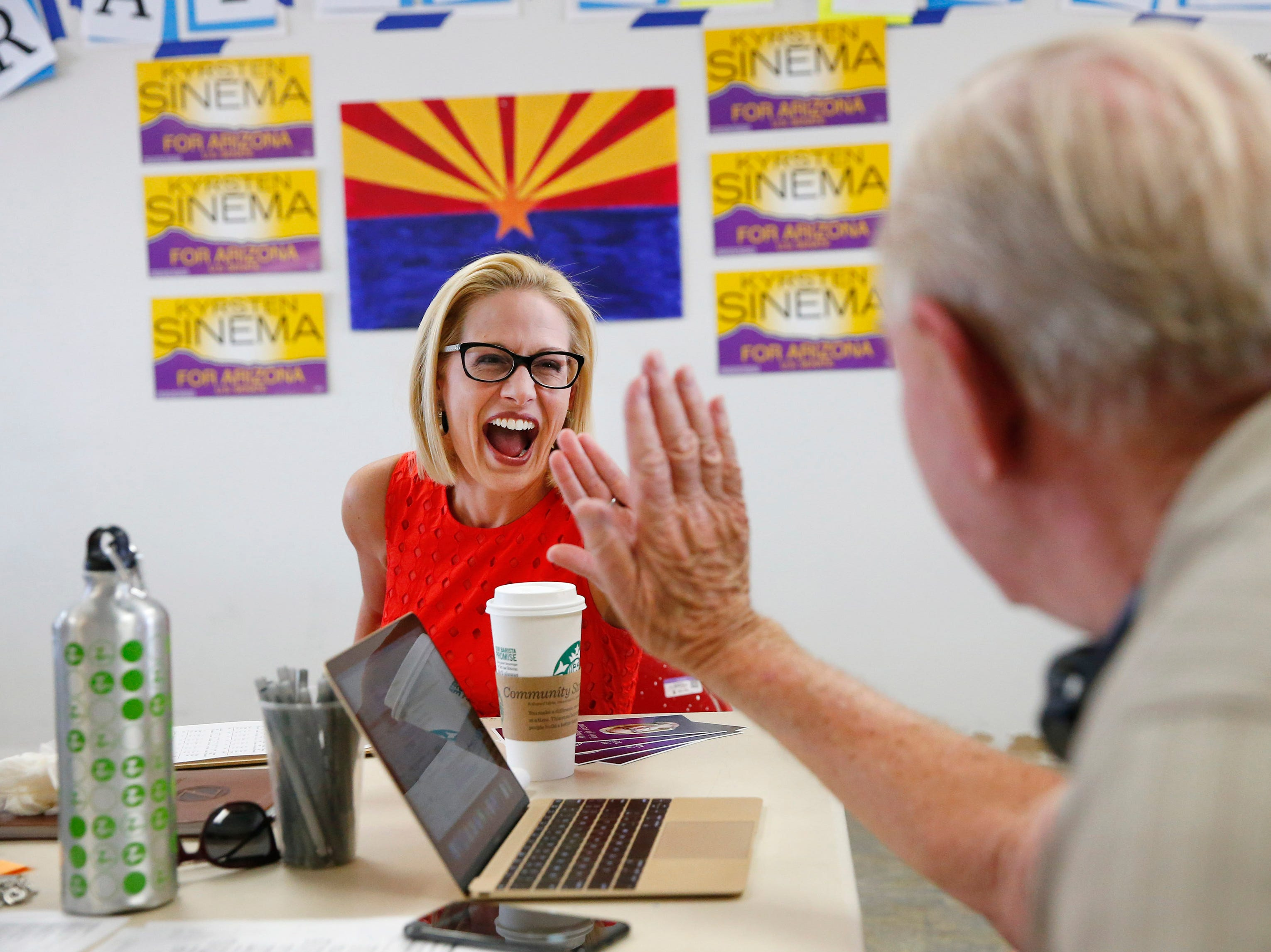 U.S. Rep. Kyrsten Sinema high-fives volunteer Bob Miller at her field office in Phoenix Aug. 28. 2018. Sinema is vying for the Democratic nomination for the open U.S. Senate seat.