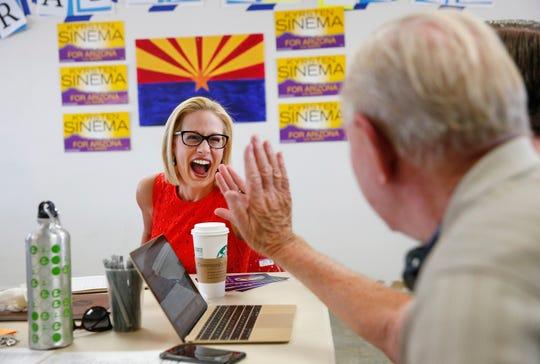 La representante Kyrsten Sinema celebra con uno de sus voluntarios en su oficina en Phoenix, tras salir vencedora en las primarias democratas, tras revelarse resultados no oficiales.