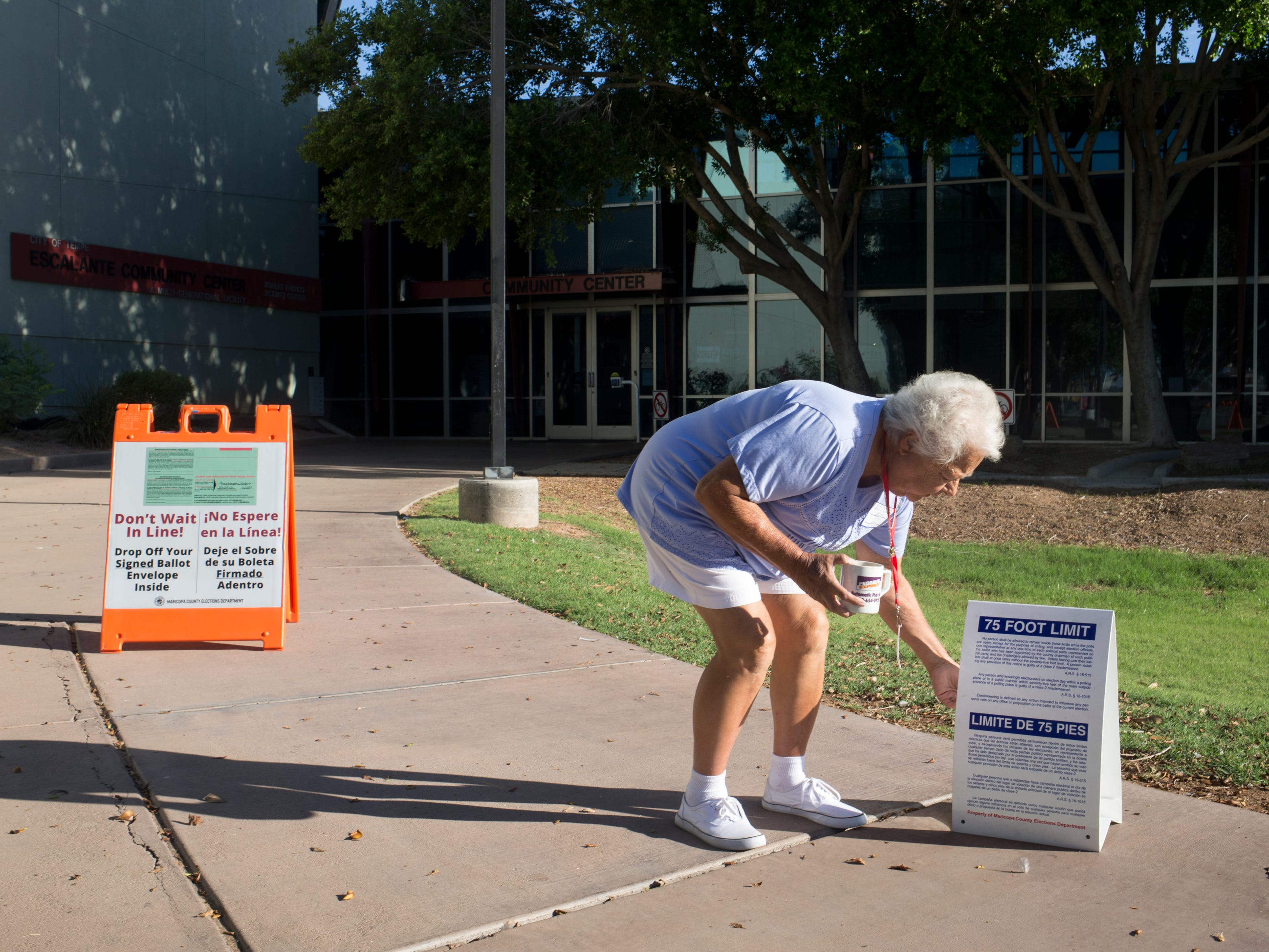 Bobbi Fredrikson, a co-inspector, sets up a voting sign, Aug. 28, 2018, at the Escalante Community Center polling place, 2150 E. Orange Street in Tempe.
