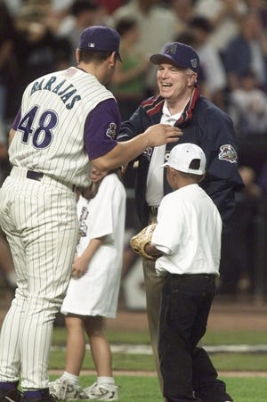 Sen. John McCain laughs with Diamondbacks catcher Rod Barajas after joining two young fans on the mound for the first pitch before Game 7 of the 2001 World Series at Bank One Ballpark.
