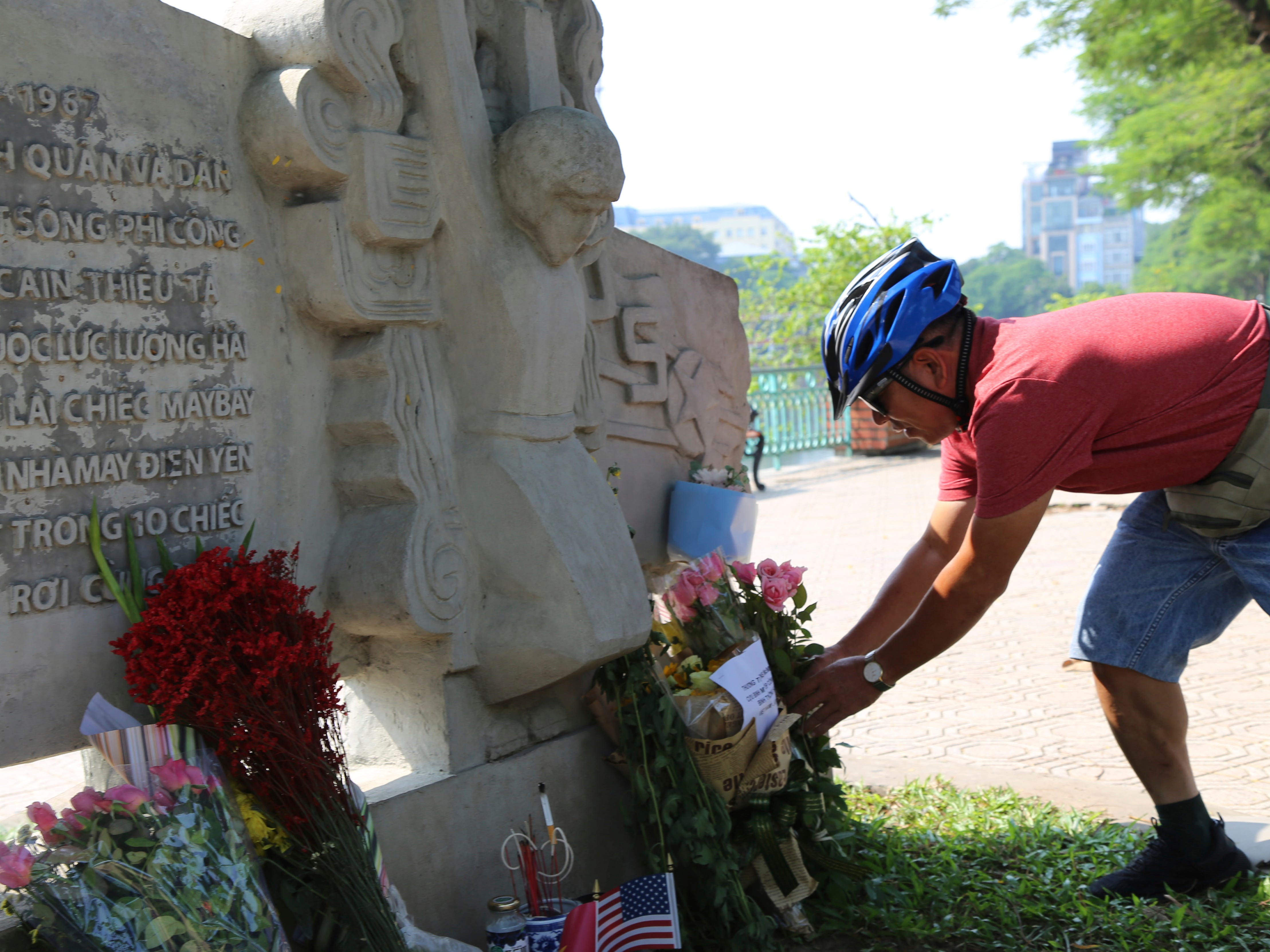 Pham Van Khanh, a 62-year-old retiree, lays flowers at the monument of Sen. John McCain in Hanoi, Vietnam, Aug. 27, 2018. The monument was erected by Vietnamese authority to mark the day when McCain's plane, a Major in the U.S. Navy was shot down in 1967.