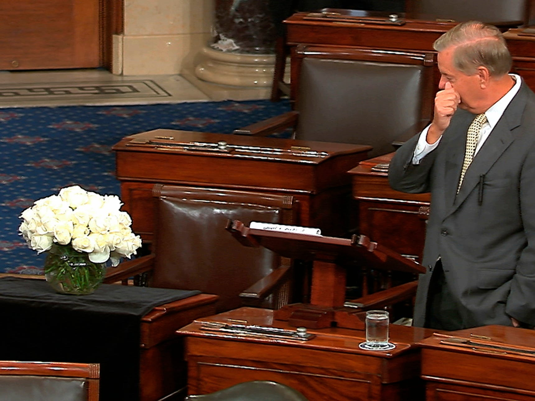 In this image from Senate Television, Sen. Lindsey Graham, R-S.C., pauses as he speaks on the Senate floor at the Capitol in Washington, Aug. 28, 2018, next to the desk of Sen. John McCain draped in black with a bowl of white roses sitting on it.