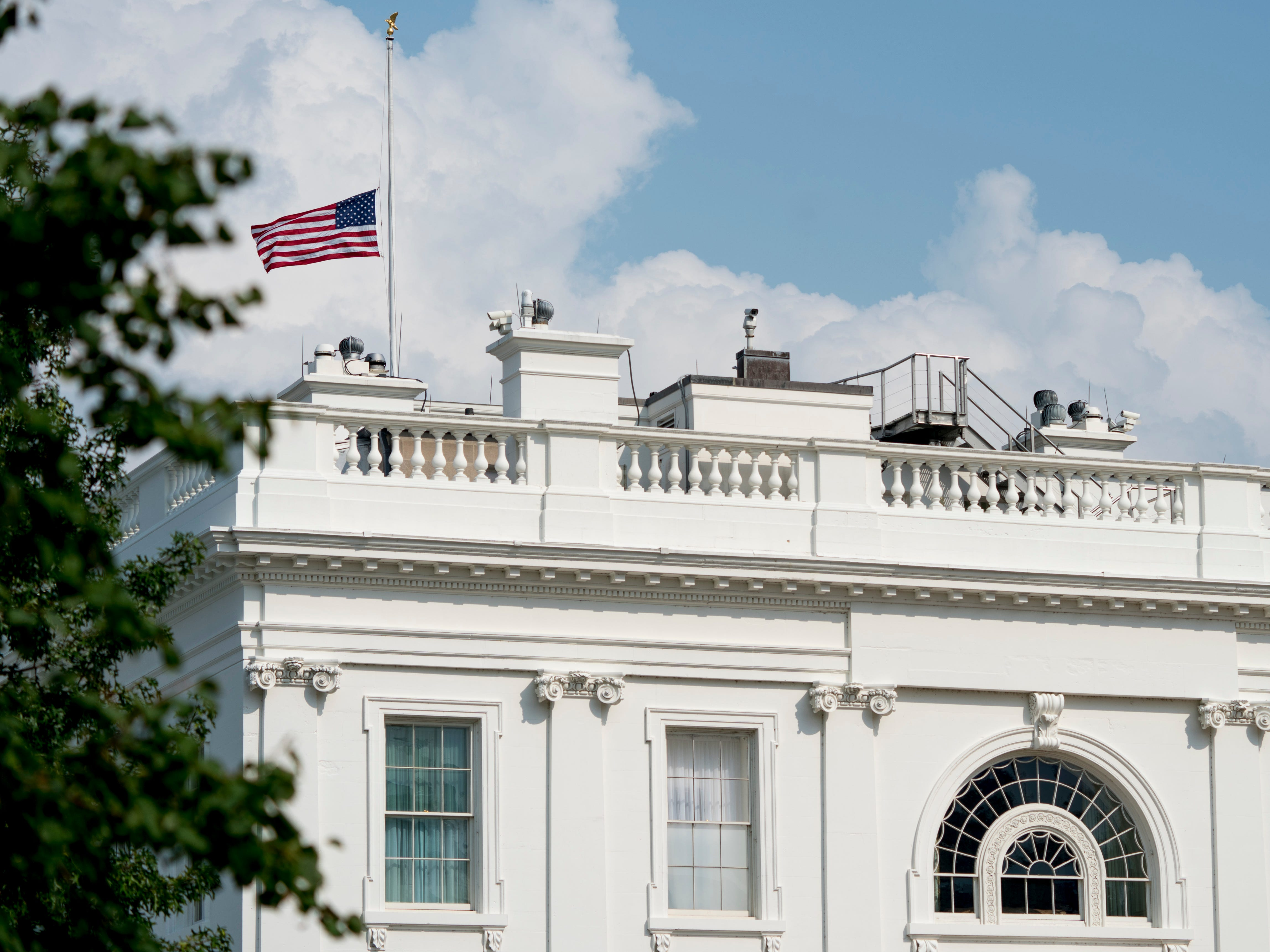 The American flag files at half-staff at the White House, Aug.. 27, 2018, in Washington. The flag atop the White House flew at half-staff over the weekend but was raised Monday and then lowered again amid criticism.
