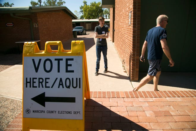 Roger Baker (right) of Scottsdale, walks back to his vehicle after voting for the primary, at the polling place at the Paiute Neighborhood Center in Scottsdale, Aug. 28, 2018.